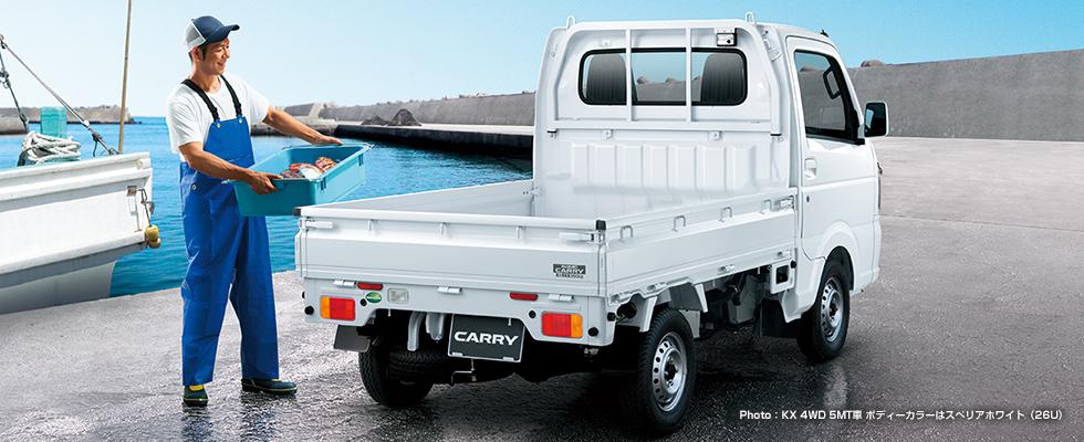 男性が海産物の入った箱をキャリイの荷台に載せようとしている様子。キャリイ KX 4WD 5MT車、ボディーカラーはスぺリアホワイト(26U)。