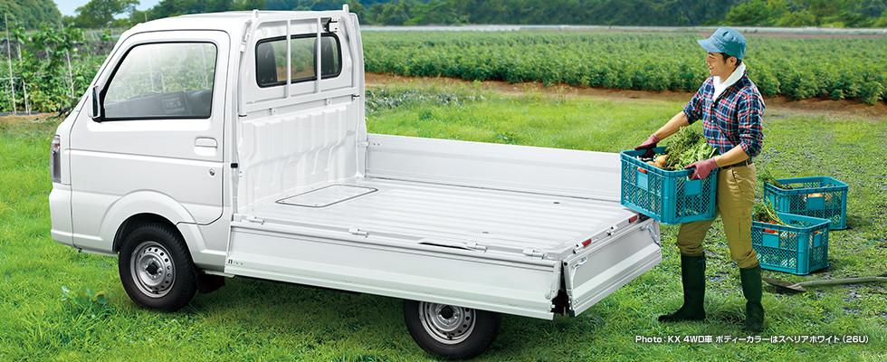 男性が野菜の入った箱をキャリイの荷台に載せようとしている様子。キャリイ KX 4WD車、カラーはスぺリアホワイト(26U)。